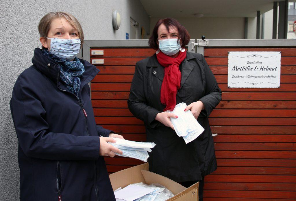 Maria Hackl (links) von von der INGENIUM-Stiftung übergibt einen Teil der vom Rotary Club Ingolstadt-Kreuztor gespendeten Masken an Patra Basner vom ambulanten Pflegedienst EVA.