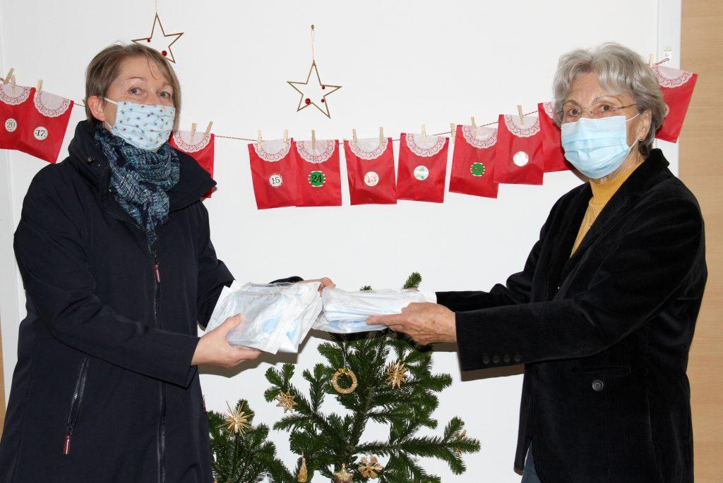 Siegrid Sukowski (rechts) nimmt die Masken für die Seniorinnen und Senioren im Betreuten Woh-nen der INGENIUM-Stiftung von Maria Hackl ent-gegen.